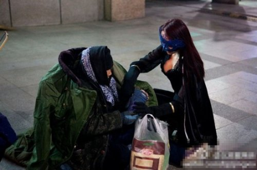 Девушка в костюме супергероя помогает бедным