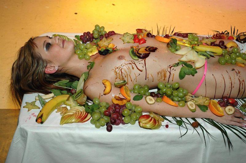 голая девушка украшенная едой в ресторане занимает