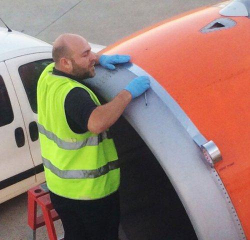 Работник аэропорта чинит турбину самолёта скотчем (2 фото)